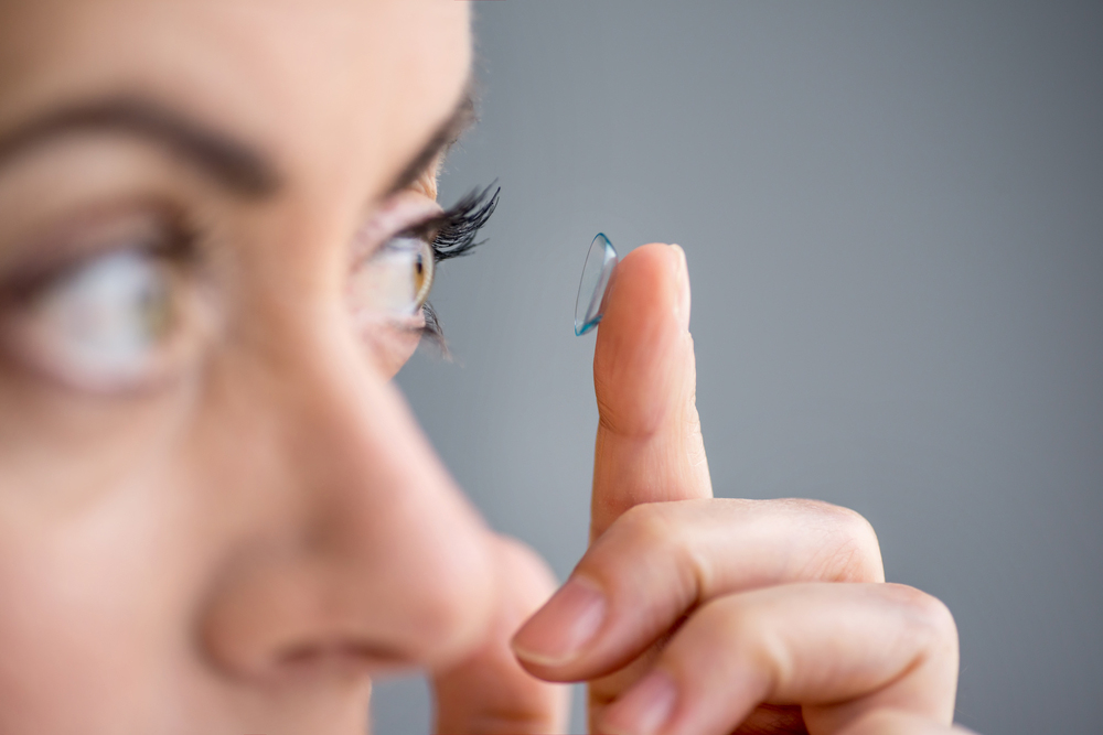 Woman putting on a contact lens